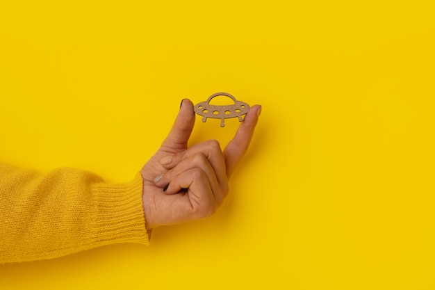 Ufo di legno in mano su sfondo giallo