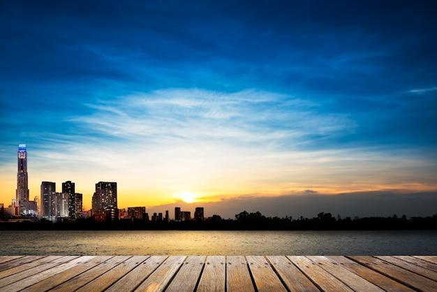 Passerella in legno in riva al fiume sulla città e morbido cielo blu al tramonto