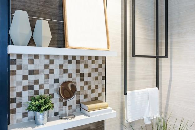 Mensola a muro in legno con elementi decorativi e asciugamano bianco pulito su un gancio Foto Premium