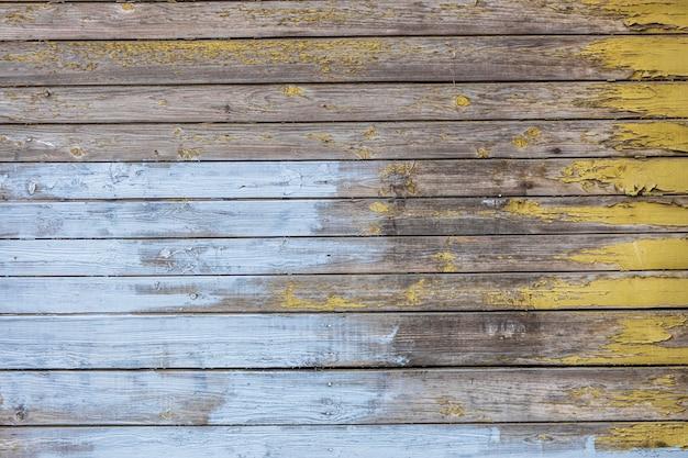 Parete in legno con assi orizzontali con vecchia vernice blu e gialla