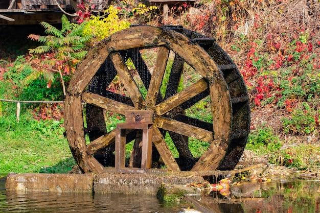 Mulino ad acqua in legno nella foresta d'autunno