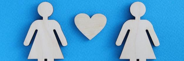 Donne in legno tra di loro cuore su sfondo blu.