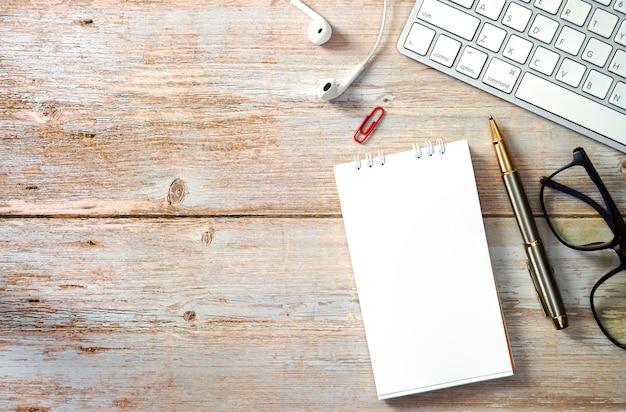 Tavolo da lavoro in legno con laptop e forniture vista dall'alto con spazio di copia piatto