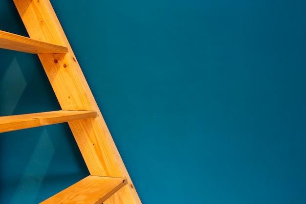Scala gialla di legno sul fondo blu della parete. colorato spazio interno astratto per il testo