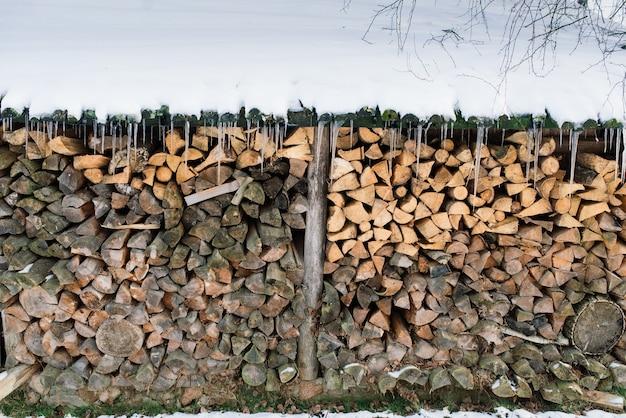 Catasta di legna da ardere alla periferia di una fattoria, cortile e bosco invernale
