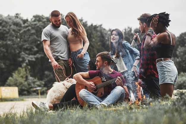 Accanto al bosco. un gruppo di persone fa un picnic sulla spiaggia. gli amici si divertono durante il fine settimana.