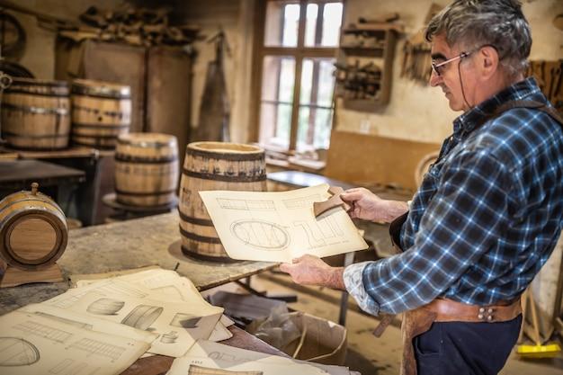Il falegname mostra il disegno, secondo il quale le botti di legno devono essere costruite in un laboratorio d'epoca.