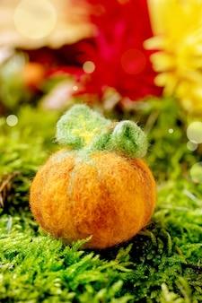 Zucca di halloween in feltro ad ago di lana su muschio. saluto di halloween stagionale di caduta