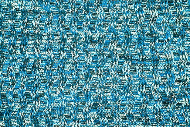 Fine di struttura della sciarpa o del maglione della lana su. sfondo blu in jersey lavorato a maglia con motivo a rilievo. trecce nel modello di maglieria a macchina