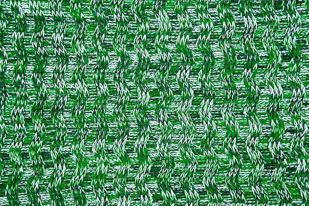 Fine di struttura della sciarpa o del maglione della lana su. verde sfondo in jersey lavorato a maglia con motivo a rilievo. trecce nel modello di maglieria a macchina
