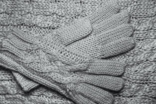 Fine di struttura del maglione o della sciarpa e dei guanti della lana su. fondo in jersey lavorato a maglia con motivo a rilievo. trecce nel modello di maglieria a macchina.