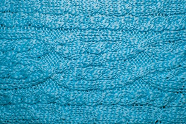 Fine di struttura del maglione o della sciarpa della lana su. fondo in jersey lavorato a maglia con motivo a rilievo