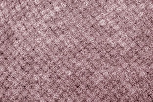 Fine di struttura del maglione di lana su. fondo in jersey lavorato a maglia con motivo a rilievo. trecce nel modello di maglieria a macchina
