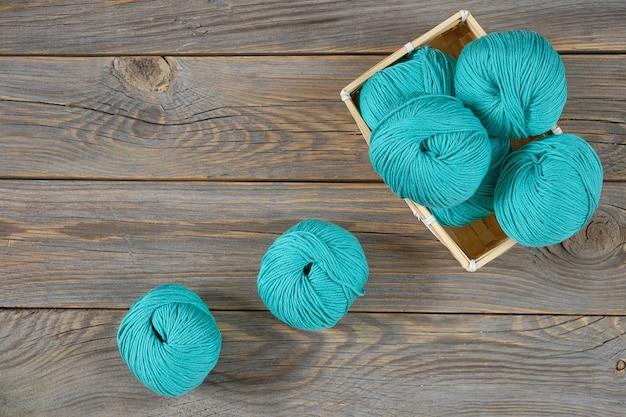 Filato di lana su un tavolo di legno e nel cestello. composizione di gomitoli di lana:, cestino di legno. comfort domestico, lavoro a maglia