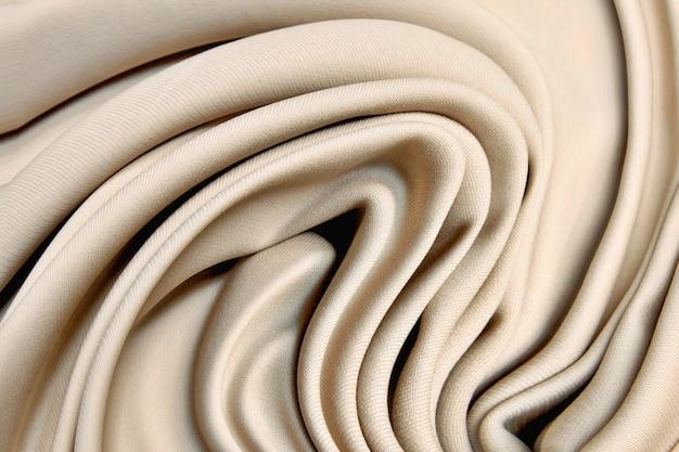 Tessuto a maglia beige di lana in morbide pieghe