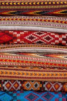 Stole di coperte di lana piegate e impilate in pile di più file la bella trama e i colori dei prodotti creano effetti sorprendenti