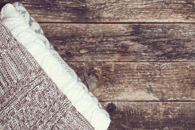 Abiti color lana, stile vintage. pila di maglieria di lana piegata. moda autunno inverno stagione, concetto di guardaroba. vestiti caldi a maglia su fondo di legno, vista dall'alto, copia dello spazio.
