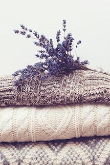 Maglioni di lana e lavanda essiccata per proteggersi dalle tarme. vestiti di lana calda lavorati a maglia. pila di vestiti a maglia caldi con lavanda. autunno, maglieria stagione invernale. armadio di casa con vestiti invernali.