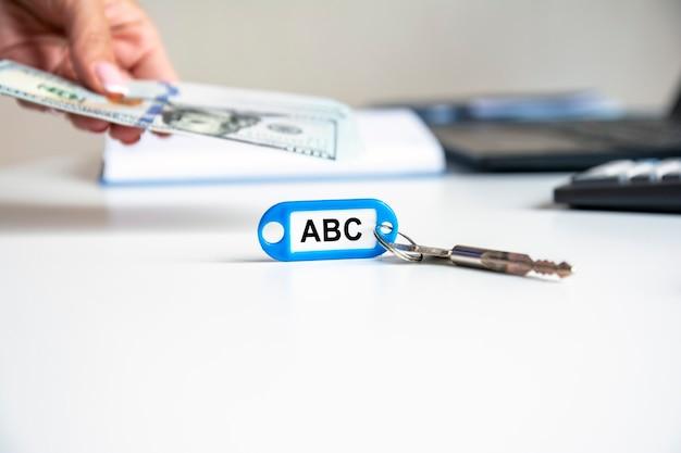 La parola abc è scritta su un portachiavi blu. la chiave è sulla scrivania dell'ufficio. sullo sfondo, la mano di una donna tiene in mano banconote. abc - ordina per essere sempre in chiusura