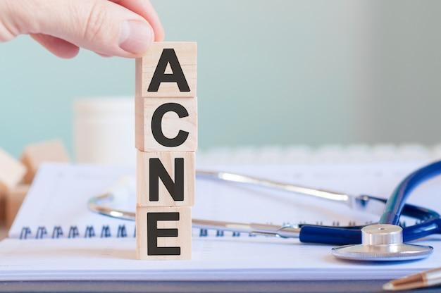 La parola acne è scritta su cubi di legno vicino a uno stetoscopio su una superficie di carta