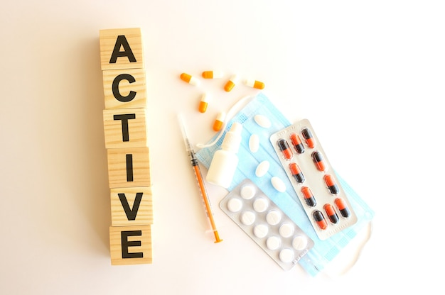La parola attivo è composta da cubi di legno su sfondo bianco con farmaci