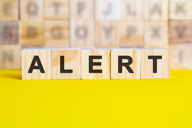 La parola avviso è scritta su cubi di legno su una superficie gialla brillante. sullo sfondo ci sono file di cubi con lettere diverse. concetto di affari e finanza