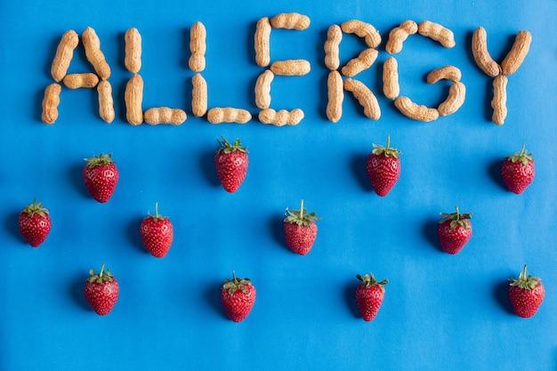 Allergia di parola firmata con arachidi con la fragola su sfondo blu