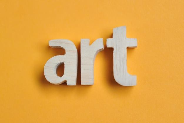 Parola art scolpita in legno. testo artistico su sfondo giallo per il tuo design, concetto.