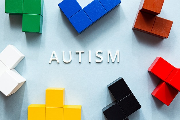 La parola autismo su sfondo blu, con vari cubi colorati.
