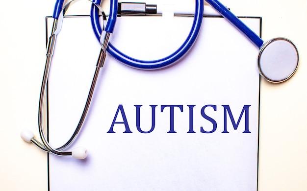 La parola autismo è scritta su un foglio bianco vicino allo stetoscopio. concetto medico.