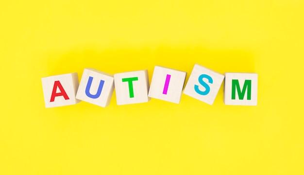 Parola autismo su cubi di legno su sfondo giallo.