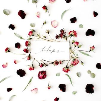 Parola autunno scritta in stile calligrafico su carta con rosa, rose rosse, eucalipto e foglie su bianco