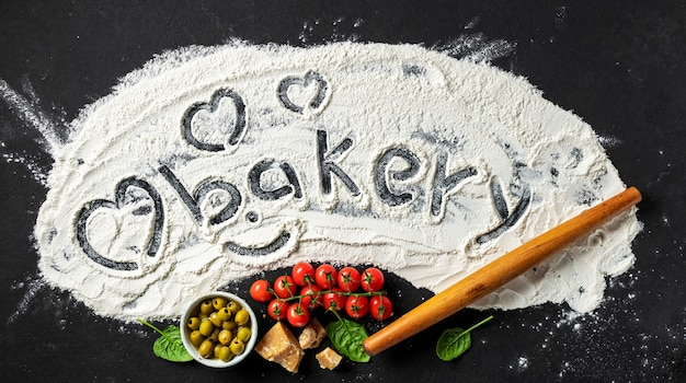 La parola panetteria e cuore è scritta su farina con mattarello e ingredienti per preparare cibo italiano, vista dall'alto. sfondo astratto di cottura