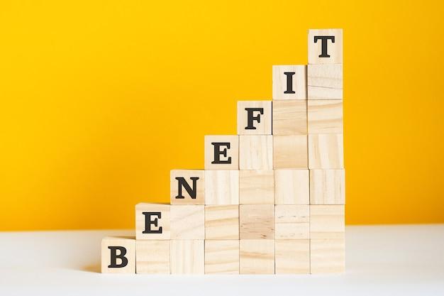 La parola beneficio è scritta su cubi di legno. blocchi su uno sfondo giallo brillante. concetto di gerarchia aziendale e marketing multilivello. messa a fuoco selettiva.