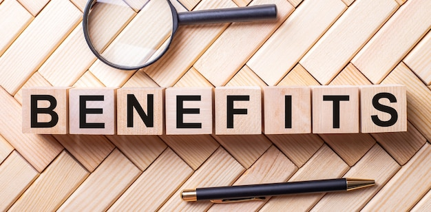 La parola benefici è scritta su cubi di legno su uno sfondo di legno accanto a un manico e una lente d'ingrandimento.