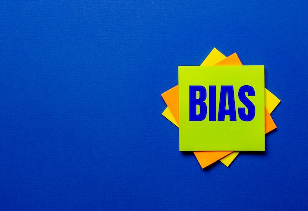 La parola bias è scritta su adesivi luminosi su una parete blu
