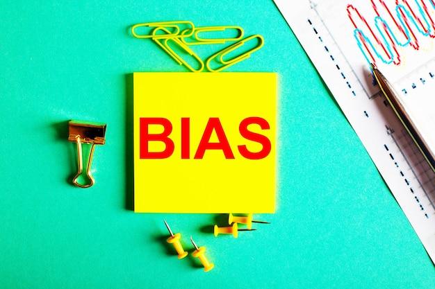 La parola bias è scritta in rosso su un adesivo giallo su sfondo verde vicino al grafico e alla matita