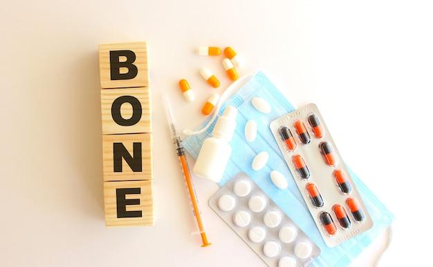 La parola bone è composta da cubi di legno su fondo bianco con farmaci e mascherina medica.