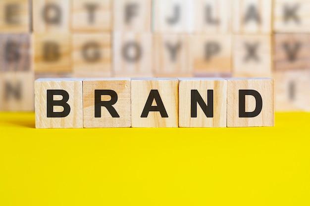 La parola brand è scritta su cubi di legno su una superficie gialla brillante. sullo sfondo ci sono file di cubi con lettere diverse. concetto di affari e finanza.