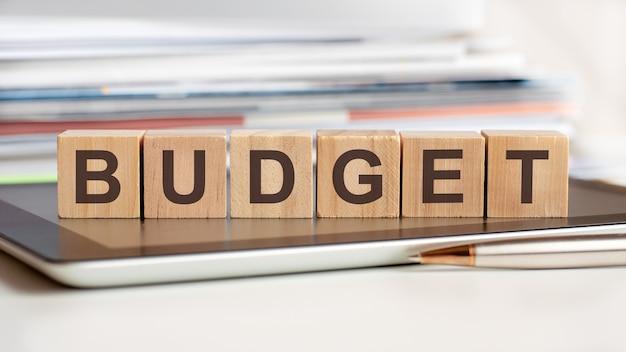 La parola budget è scritta su cubi di legno in piedi su un blocco note, sullo sfondo una pila di documenti, messa a fuoco selettiva. può essere utilizzato per affari, istruzione, concetto finanziario.