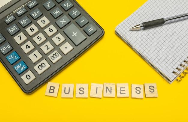 Affari di parola realizzati con lettere di legno su calcolatrice gialla e moderna con penna e taccuino.