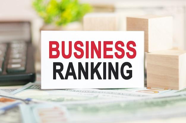 La parola classifica aziendale è scritta su carta di carta bianca vicino a cubi di legno, calcolatrice su banconote .concetto aziendale e finanziario