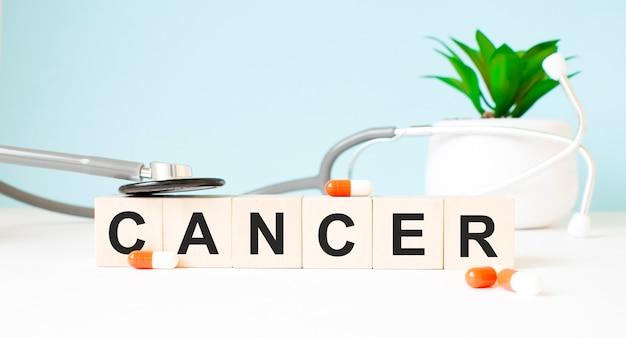 La parola cancro è scritta su cubi di legno vicino a uno stetoscopio su uno sfondo di legno. concetto medico