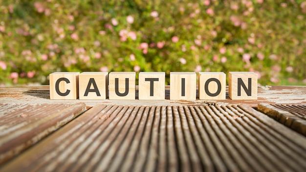 La parola cautela è scritta su cubi di legno. i blocchi sono posti su una vecchia tavola di legno illuminata dal sole. sullo sfondo c'è un arbusto in fiore brillante