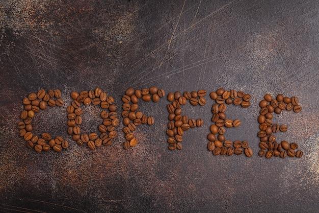 Parola caffè a base di chicchi di caffè, sfondo scuro arrugginito, vista dall'alto, copia dello spazio.