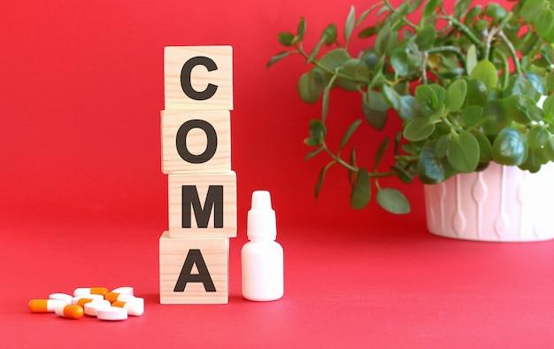 La parola coma è composta da cubi di legno su una superficie rossa con farmaci