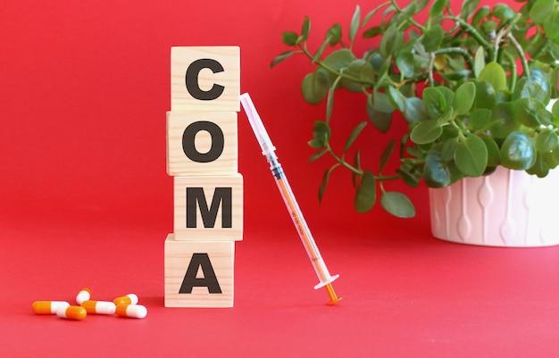 La parola coma è composta da cubi di legno su fondo rosso con farmaci.