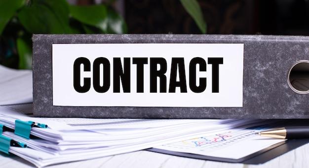 La parola contratto è scritta in una cartella di file grigia accanto ai documenti. concetto di affari