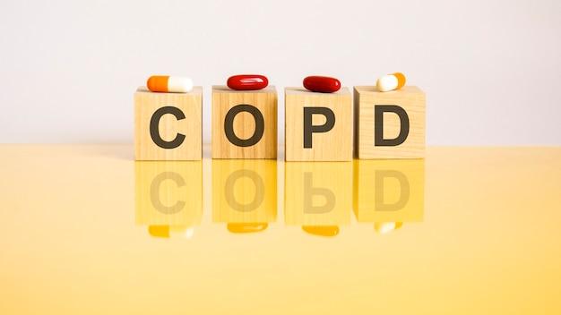 La parola bpco è composta da cubi di legno su uno sfondo giallo con pillole. concetto medico di trattamento, prevenzione ed effetti collaterali. bpco - abbreviazione di broncopneumopatia cronica ostruttiva