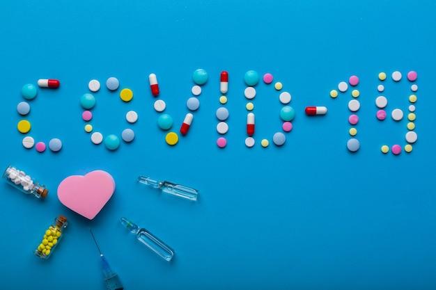 Parola covid19 scritta con pillole su sfondo blu con iniezione come concetto di vaccinazione